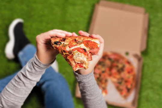 A slice of pizza in female hands. Lunch on the green grass