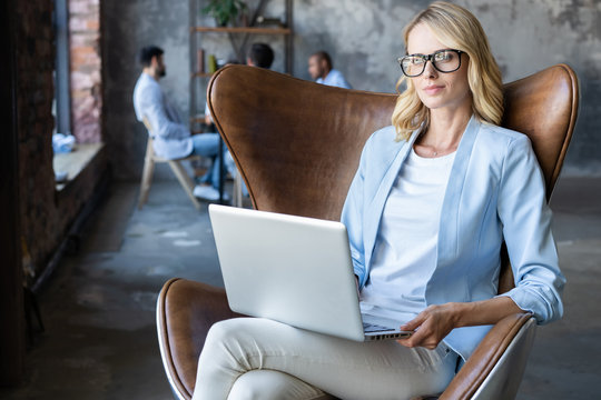 Image of cheerful office woman with blond hair in business wear sitting on chair and working with laptop office.