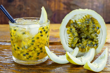 Caipirinha drink, made of cachaça and passion fruit. Traditional alcoholic drink from Brazil wood background. Image with space for text.