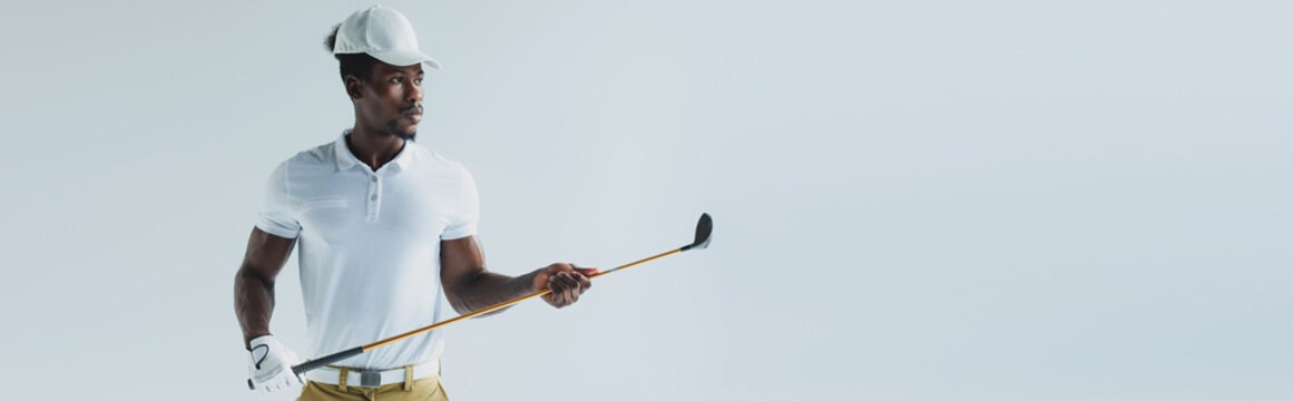 panoramic shot of handsome african american sportsman holding golf club isolated on grey