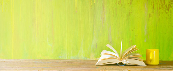 open book and a cup of coffee on green grungy background,reading, education, literature,learning,...
