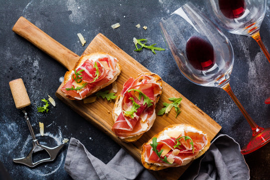 Open ham sandwiches, arugula and hard cheese, served on  wooden stand with aglass of red wine on aconcrete old dark background. Rustik style. Top view.
