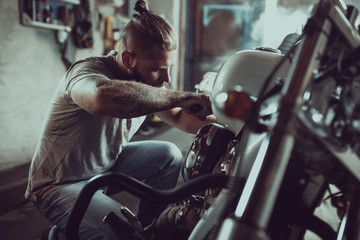Handsome bearded man repairing his motorcycle in the garage. A man wearing jeans and a t-shirt Fototapete