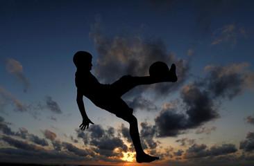 A boy kicks a soccer ball on a beach in Colombo