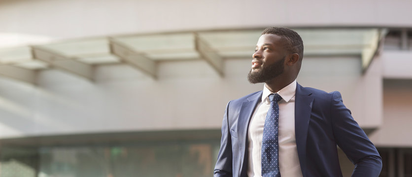 African businessman looking away standing in front of office building