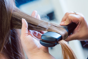 Hairdresser using flat iron on hair of woman customer