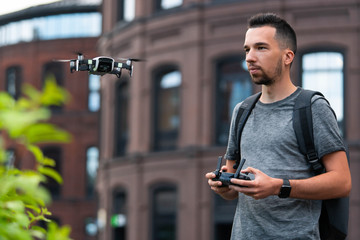 Young handsome man launching drone quadcopter at urban background.