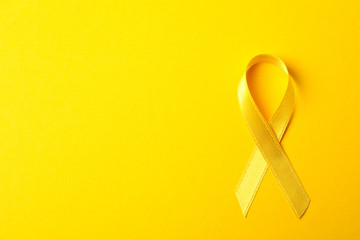 Yellow awareness ribbon on color background, space for text Wall mural