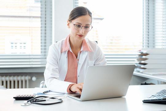 Doctor doing paperwork on computer sitting on desk
