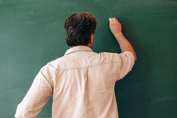 Teacher write on the blackboard and explain a lesson. Back view- Image