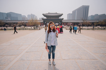 Young woman treveler with guide book on hand in gyeongbokgung palace between travel in south korea.