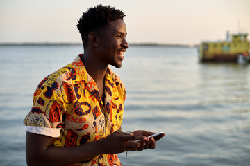 Young man standing at the sea, holding smartphone, portrait