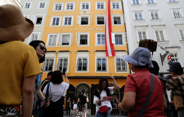 Tourists take a picture in front of Wolfgang Amadeus Mozart's birth house in Salzburg