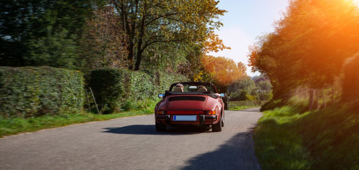 sports car drinving on a road on summer day