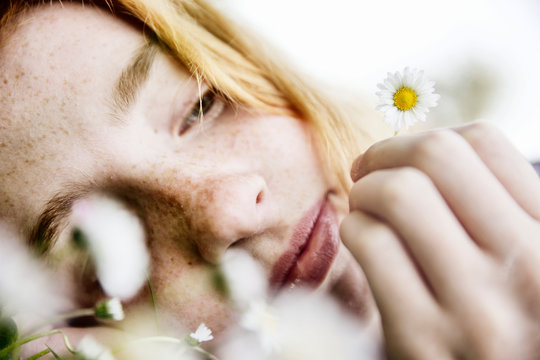 Close up of girl holding daisy flower