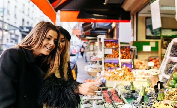 France, Paris, two young women at a street market in Montmartre