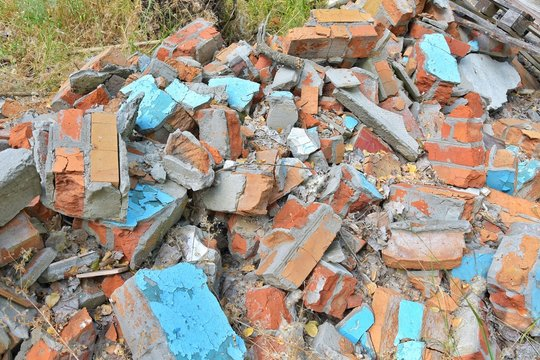 Pile of construction waste with old broken red bricks and broken boards. Rubbish from a ruined house with bricks pieces and old timber. Junk yard outdoor. Old building materials polluting environment