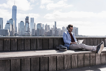 USA, man wearing headphones using tablet at New Jersey waterfront with view to Manhattan
