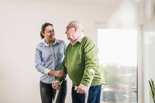 Young woman supporting senior man walking on crutches