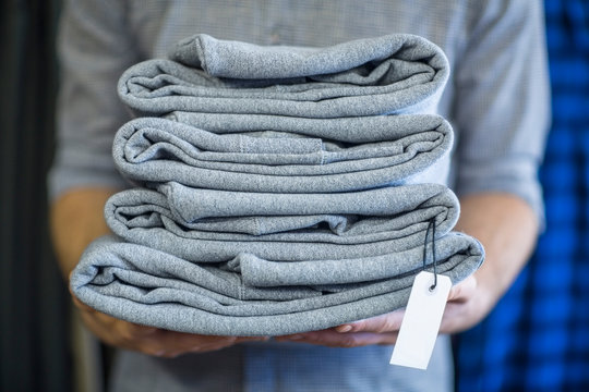 Man holding stack of folded clothes