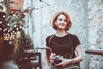 Young hipster female journalist with retro camera  sits on a chair and smiles outdoors against the backdrop of garlands