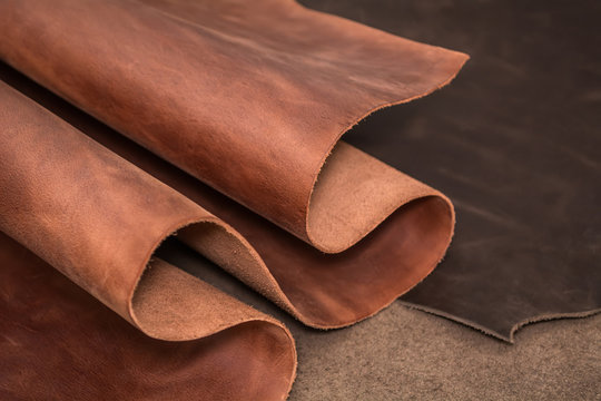 Rolls of natural brown and black leather. Materials for leather craft