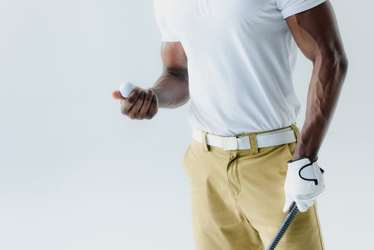 cropped view of african american golf player holding ball isolated on grey