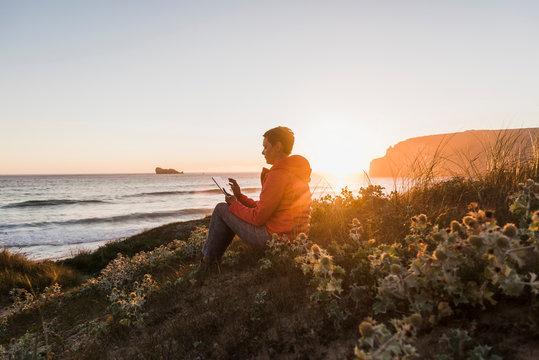 France, Bretagne, Crozon peninsula, woman sitting at the coast at sunset using tablet