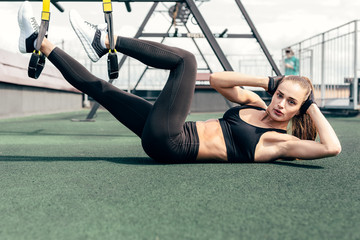 Fitness woman doing crunches while lying on a roof using suspension straps for legs