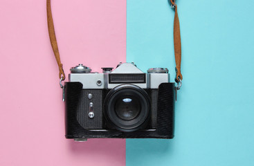 Vintage retro film camera in leather cover with strap on pink blue pastel background. Top view