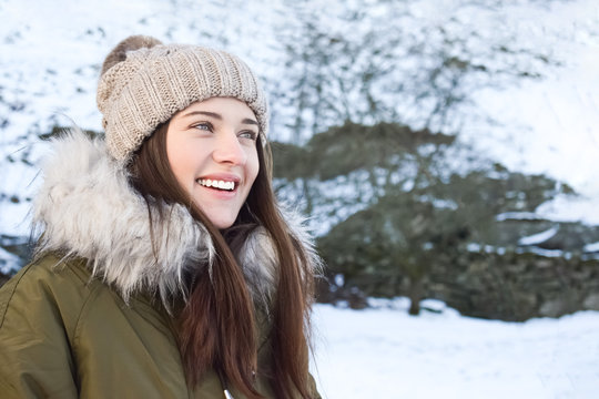 Portrait of a girl in a hat with a pompon against the background of a winter landscape. Beautiful woman 25 years old in a winter park. Close up. Copy space