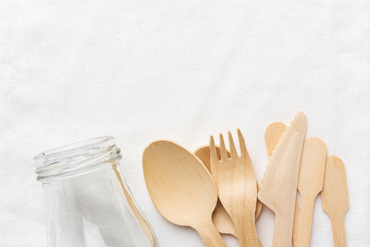 Glass bottle wooden cutlery spoon fork knife on white cotton textile background. Zero waste reusable biodegradable eco friendly materials environment protection concept