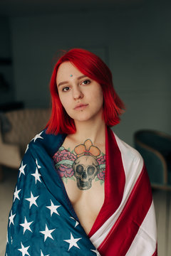 Portrait of young woman with tattoo wrapped in American Flag