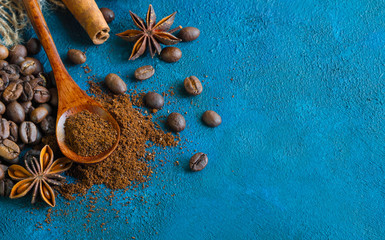 coffee grains scattered on a blue textural background, anise stars, cinnamon sticks and ground coffee in a wooden spoon. Top view