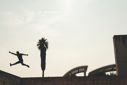 Silhouette of young hispanic break dancer performing a dance pose in the street at sunset surrounded by palm tree