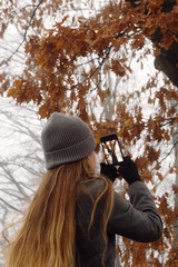 Anonymous woman taking picture of autumn tree
