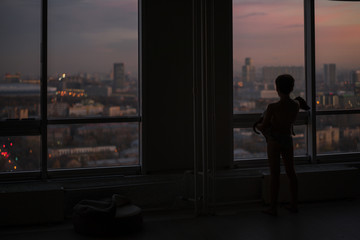 A boy with a dog in a room with a beautiful view from the window