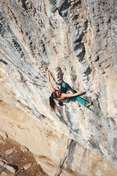 Young climber woman climbing a steep overhanging tufa limestone wall, Oliana, Spain