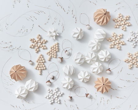 Beautiful pattern of origami paper balls, dry twigs, wooden stars and Christmas trees on a gray background. Christmas layout. Flat lay
