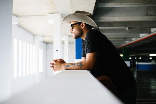 Modern man in hat standing on parking