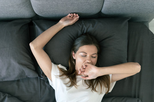 Young adult woman sleeping on bed in morning