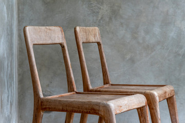 A Couple Of Chairs in front of a cement wall