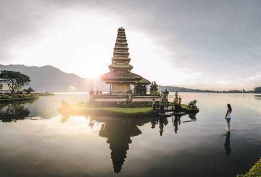beautiful woman standing in a lake looking at a balinese water temple at sunrise