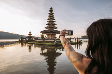 close up of a woman taking a picture with her smartphone from a balinese water temple