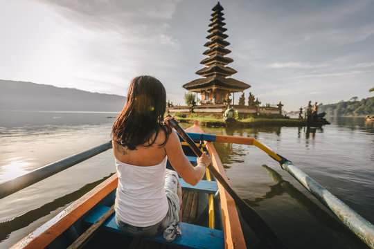 young beauty paddling in fishing boat at sunrise with balinese temple in the back