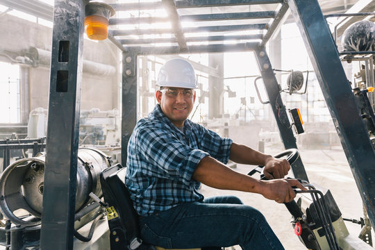 Portrait of Hispanic man at Work on Forklift
