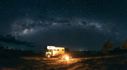 panorama shot of a family sitting at a bonfire under the milky way with a camping truck