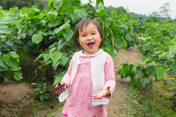 little asian girl eating mulberry outdoor