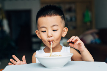 Boy eating spaghetti at home