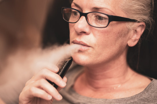 middle aged woman is exhaling vape smoke while thinking about her life